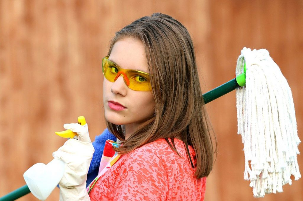 Girl with mop, safety glasses, and cleaning supplies